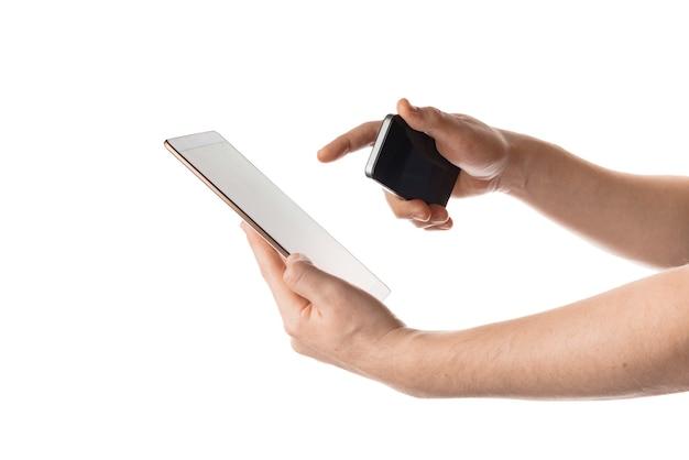 Homem segura o telefone preto e toca no tablet branco ao mesmo tempo. isolado em um fundo branco.