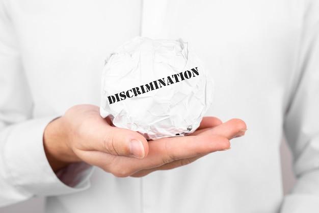 Homem segura papel amassado com o texto discriminação nas mãos