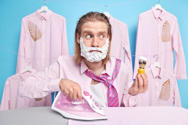 Homem segura pincel de barbear aplica espuma de gel ferros roupas se prepara para o encontro quer fazer poses brilhantes em camisas passadas em cabides estando ocupado depois de dormir