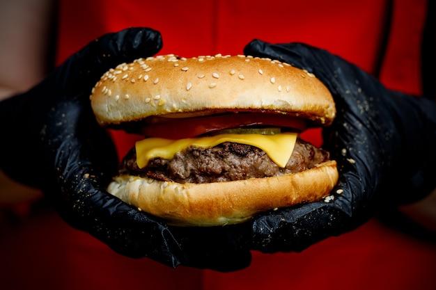 Homem segura saboroso hambúrguer pronto nas mãos em luvas pretas.