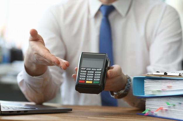 Homem segura seu terminal sem fio de mão para pagamento