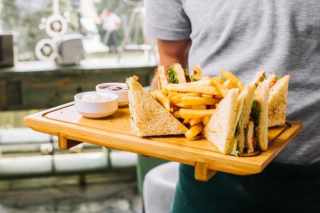 Homem segura, tábua madeira, sanduíche clube, brinde, pão, tomate galinha, pepino, batatas fritas maionese, ketchup, vista lateral