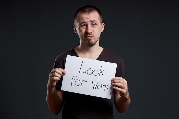 Homem segura um cartaz com as palavras procurando trabalho, desemprego e crise