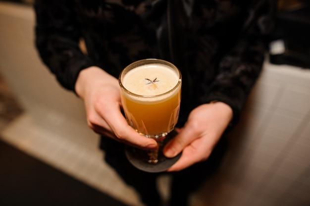 Homem segura um copo de cristal com uma mistura azeda de coquetel alcoólico