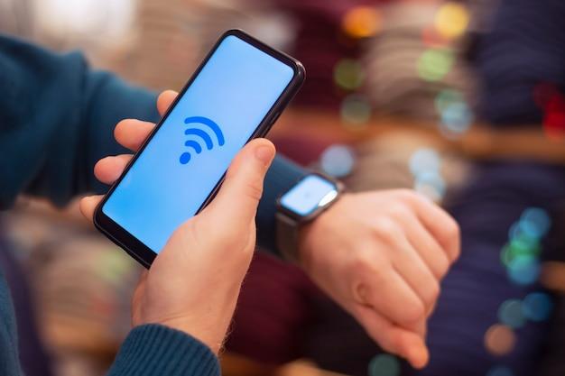Homem segura um smartphone com um ícone de close-up de wi-fi e um relógio inteligente na mão.