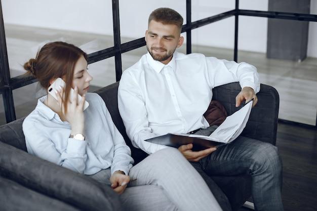 Homem segura uma pasta. parceiros de negócios em uma reunião de negócios. mulher falando ao telefone