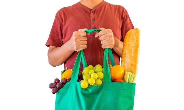 Homem segura uma sacola de compras reutilizável ecologicamente correta, cheia de produtos de mercearia completos com frutas e vegetais frescos