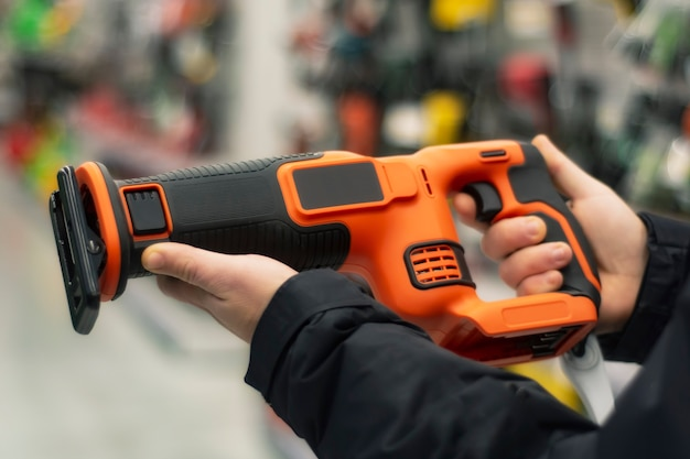 Homem segura uma serra alternativa laranja para reparos no cenário de vitrines de uma loja de ferragens.