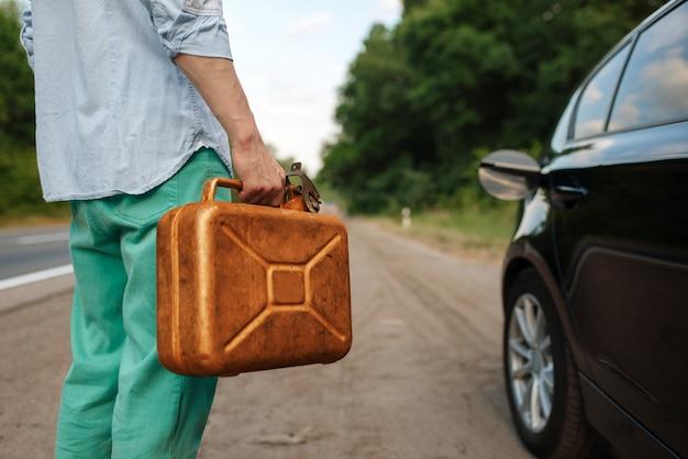 Homem segura vasilha de gasolina, quebra do carro, sem gasolina. automóvel quebrado ou problema com veículo, problema com automóvel na rodovia