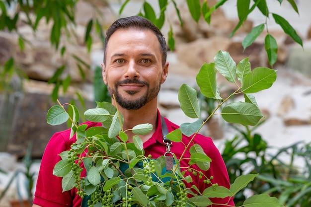 Homem segurando a árvore jovem e prepare-se para plantar no solo.
