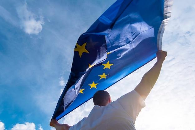Homem segurando a bandeira da ue ou bandeira da união europeia, imagens de conceito