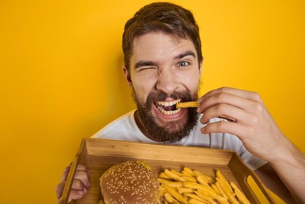 Homem segurando a bandeja com hambúrguer e batatas fritas