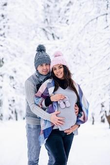 Homem segurando a barriga de grávida de uma mulher e a mulher segurando sapatos de bebê enquanto eles estão no parque de inverno nevado