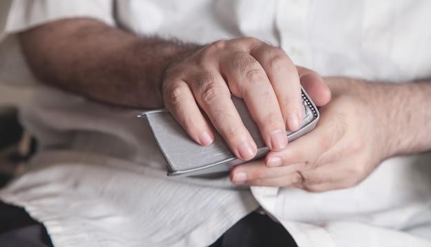 Homem segurando a bíblia em casa. religião