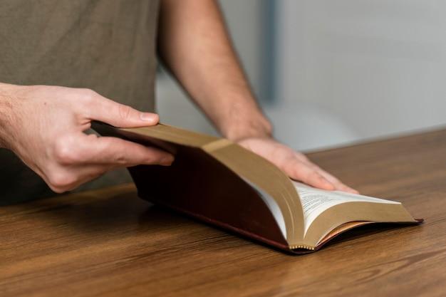 Homem segurando a bíblia na mesa