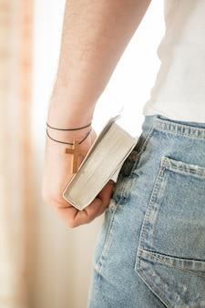 Homem segurando a bíblia sagrada sobre um fundo cinza para o conceito de cópia para religião, oração, educação e estudo da bíblia