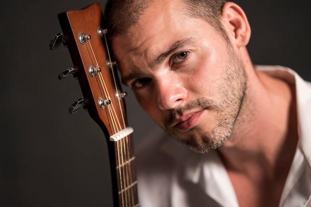 Homem segurando a cabeça no cabeçote da guitarra e olhando