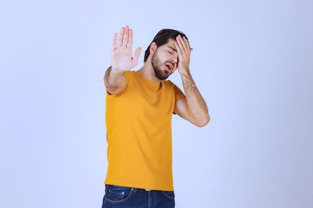 Homem segurando a cabeça porque está com dor de cabeça