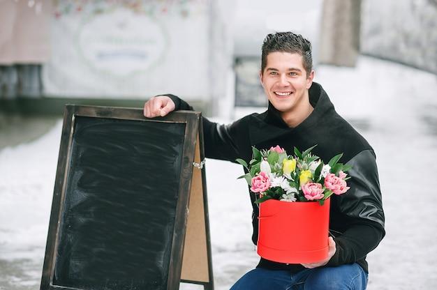 Homem segurando a caixa de presente vermelha com um lindo buquê de florescência tulipas cor de rosa, amarelas e brancas e crisântemos brancos com folhas verdes, ao ar livre