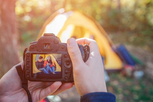 Homem segurando a câmera que tira foto do casal. eles se sentam na tenda.