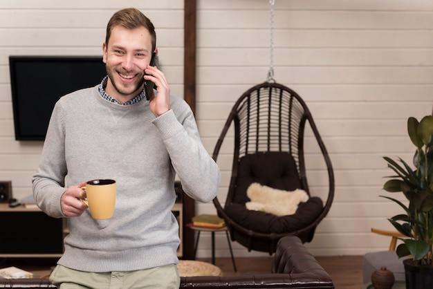Homem segurando a caneca e falando ao telefone em casa