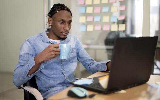 Homem segurando a caneca e trabalhando no laptop no escritório