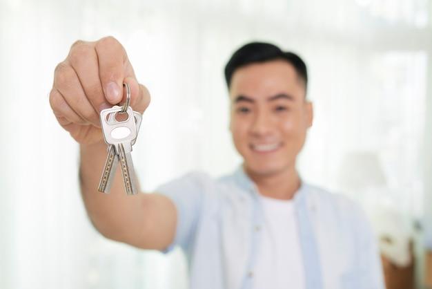 Homem segurando a chave do apartamento novo