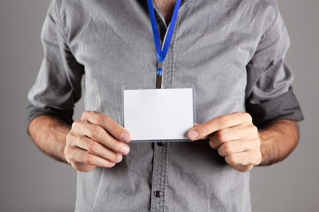Homem segurando a etiqueta de identificação em fundo cinza