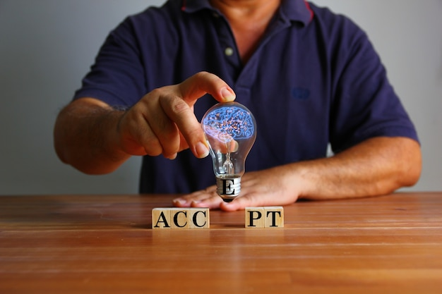 Homem segurando a lâmpada com ilustração do cérebro na mão com texto aceita no bloco de madeira. a adoção de novas ideias no trabalho continuará a desenvolver negócios indefinidamente, conceito de ideia