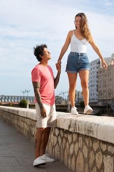 Homem segurando a mão da namorada ao ar livre