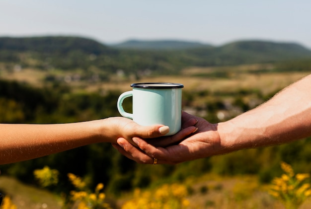 Homem segurando a mão de uma mulher e uma xícara de café