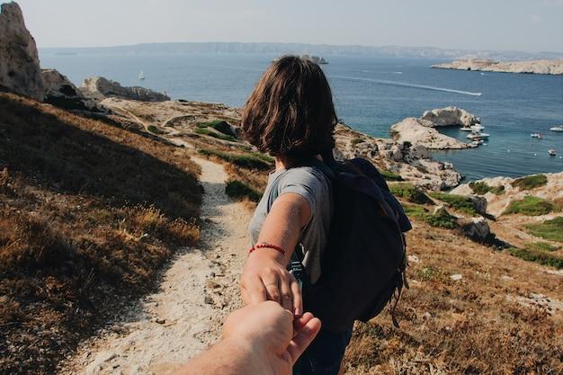 Homem segurando a mão de uma mulher perto do mar durante o dia
