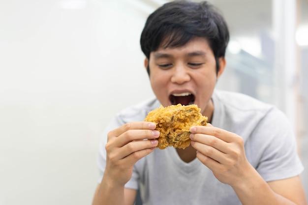 Homem segurando a mão e mostrando farinha de frango frito para comer