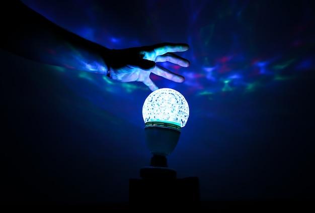 Homem segurando a mão sobre a lâmpada da noite. sombras azuis nas paredes. conceito de adivinhação espiritual.