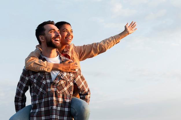 Homem segurando a namorada nas costas com espaço de cópia