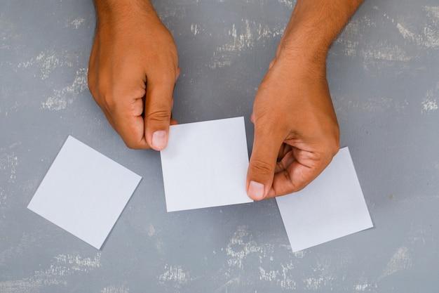 Homem segurando a nota pegajosa.