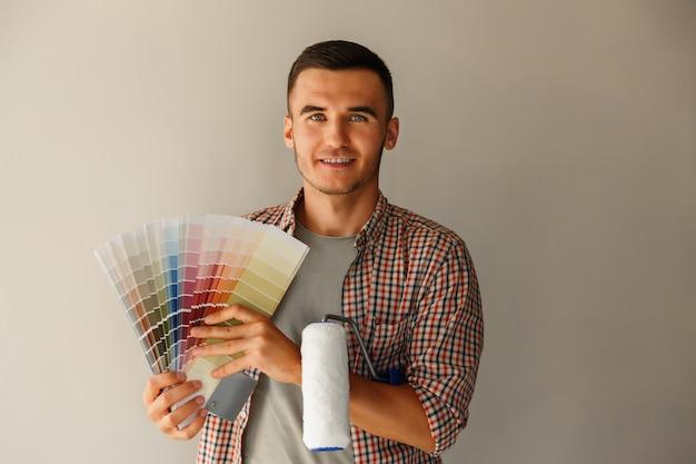 Homem segurando a paleta de cores e rolo de pintura