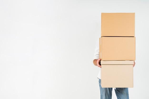 Homem segurando a pilha de caixas de papelão com espaço de cópia
