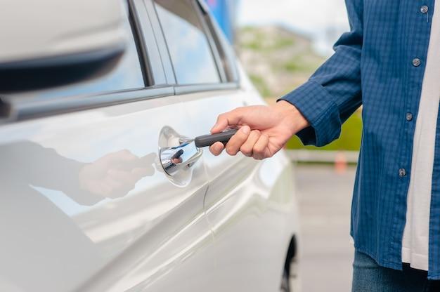 Homem segurando a porta do carro abrindo a chave