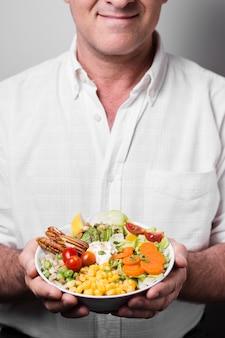 Homem segurando a tigela de comida saudável