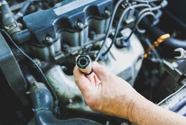 Homem segurando a vela de ignição no motor de um carro antigo. detalhes internos da máquina. reparação de veículo.