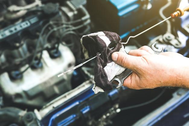 Homem segurando a vela de ignição no motor de um carro antigo. nível de óleo no tanque. detalhes internos da máquina. reparação de veículo.