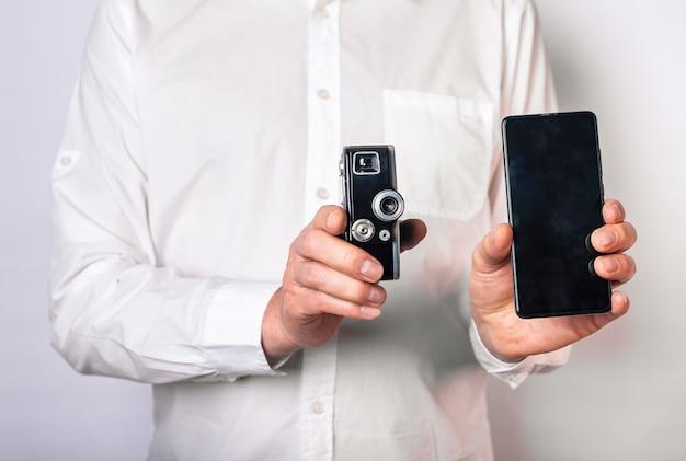 Homem segurando a velha câmera retro e o novo smartphone ou telefone. lente vintage vs telefone móvel.
