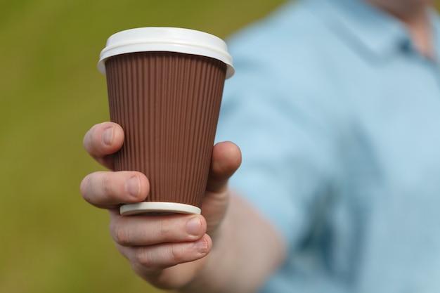 Homem segurando a xícara de café de papel vazio. maquete de modelo