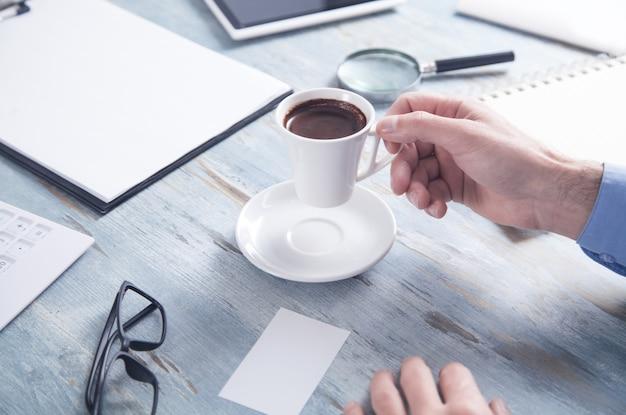 Homem segurando a xícara de café na mesa do escritório.