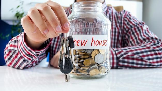 Homem segurando as chaves da nova casa e o frasco de vidro cheio de moedas. conceito de investimento financeiro, crescimento da economia e poupança bancária