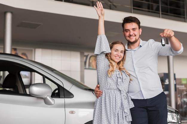 Homem segurando as chaves do carro e mulher levantando a mão