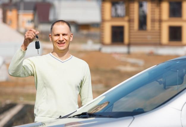 Homem segurando as chaves do carro no fundo da casa