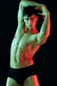 Homem segurando as mãos atrás da cabeça em um fundo preto e calcinha cortada modelo de luz de néon