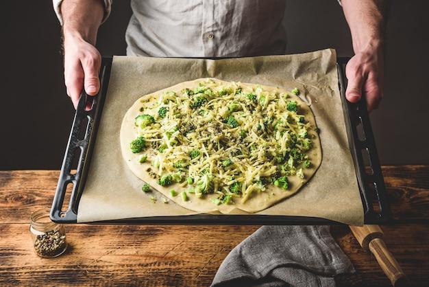 Homem segurando assadeira com pizza crua com brócolis, molho pesto, temperos e queijo